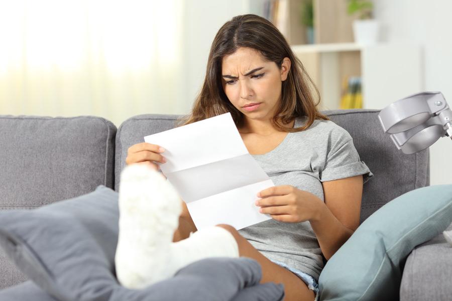 Woman in foot cast reading bill